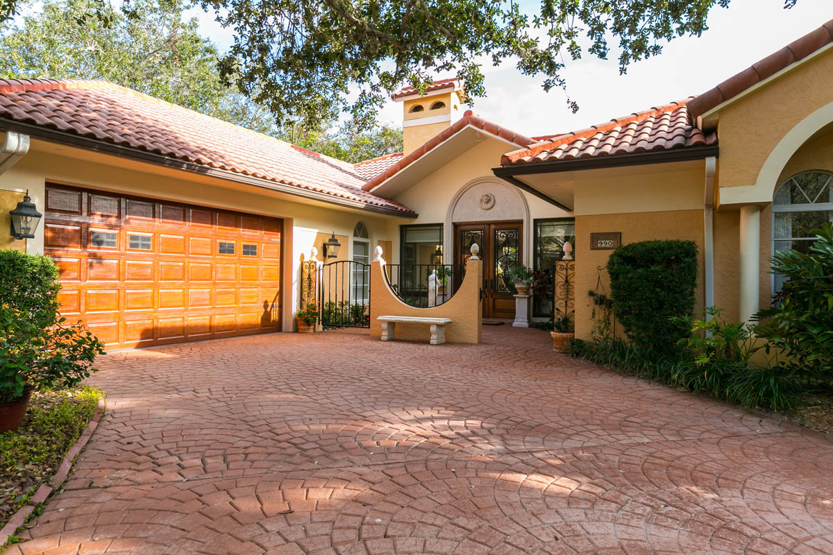 An impressive front entrance with wood-grained garaged door, entryway with water fountain and custom designed front door